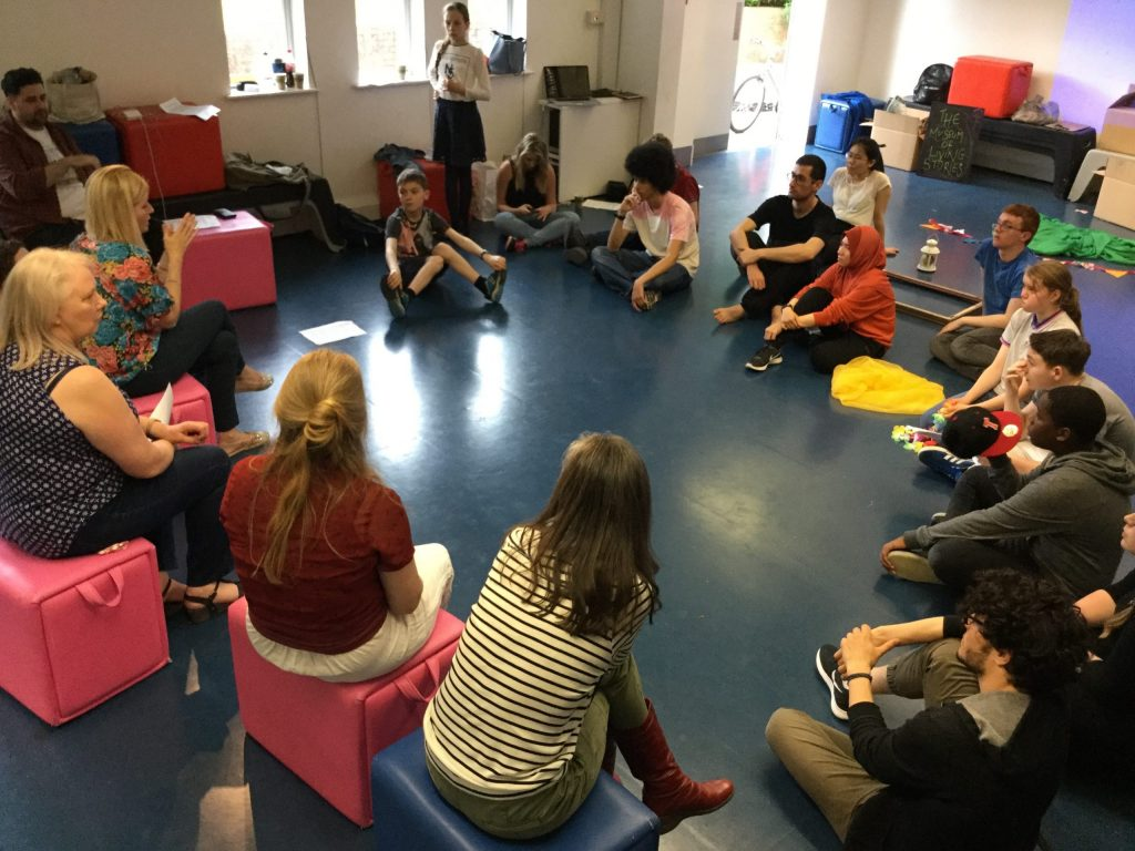 Students sitting on the floor in a circle with their teacher in Coventry, England