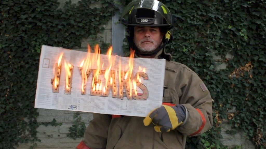 Image of Paul Gross dressed as a fire fighter to draw attention to the climate emergency