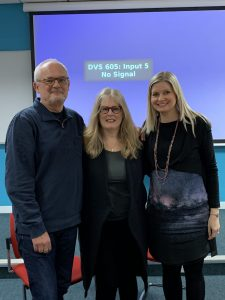 Dr. Kathleen Gallagher, Dr. Rachel Turner-King and Professor Jonothon Neelands posing in front of a projector screen after a presentation