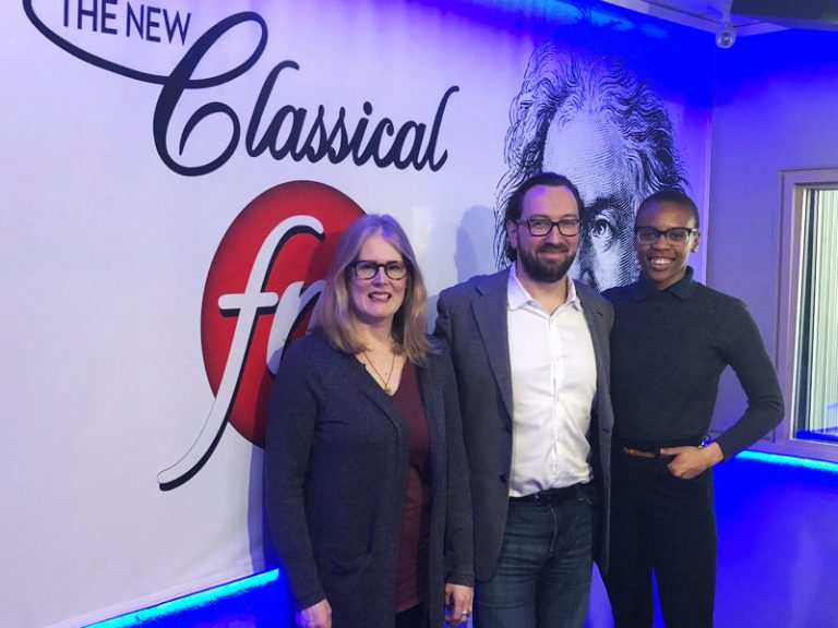 Image of Dr. Kathleen Gallagher, Amaka Umeh and Marc Wigmore in front of a white wall with the Classical FM logo, for the radio show The Oasis