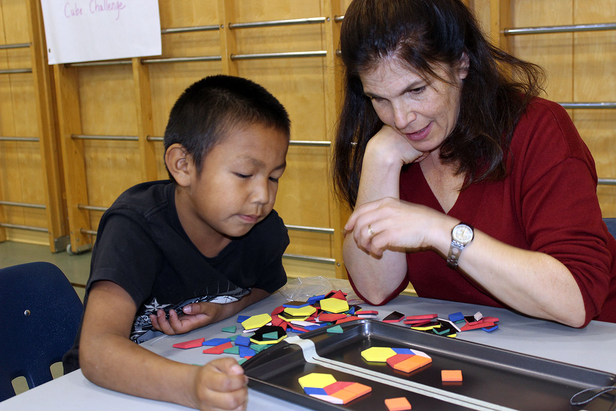 Jackman ICS's Carol Stephenson plays math games with a student at the Pegamigabo Family Math Party