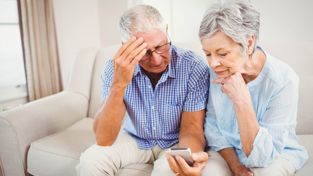 Worried elderly couple looking at a cell phone