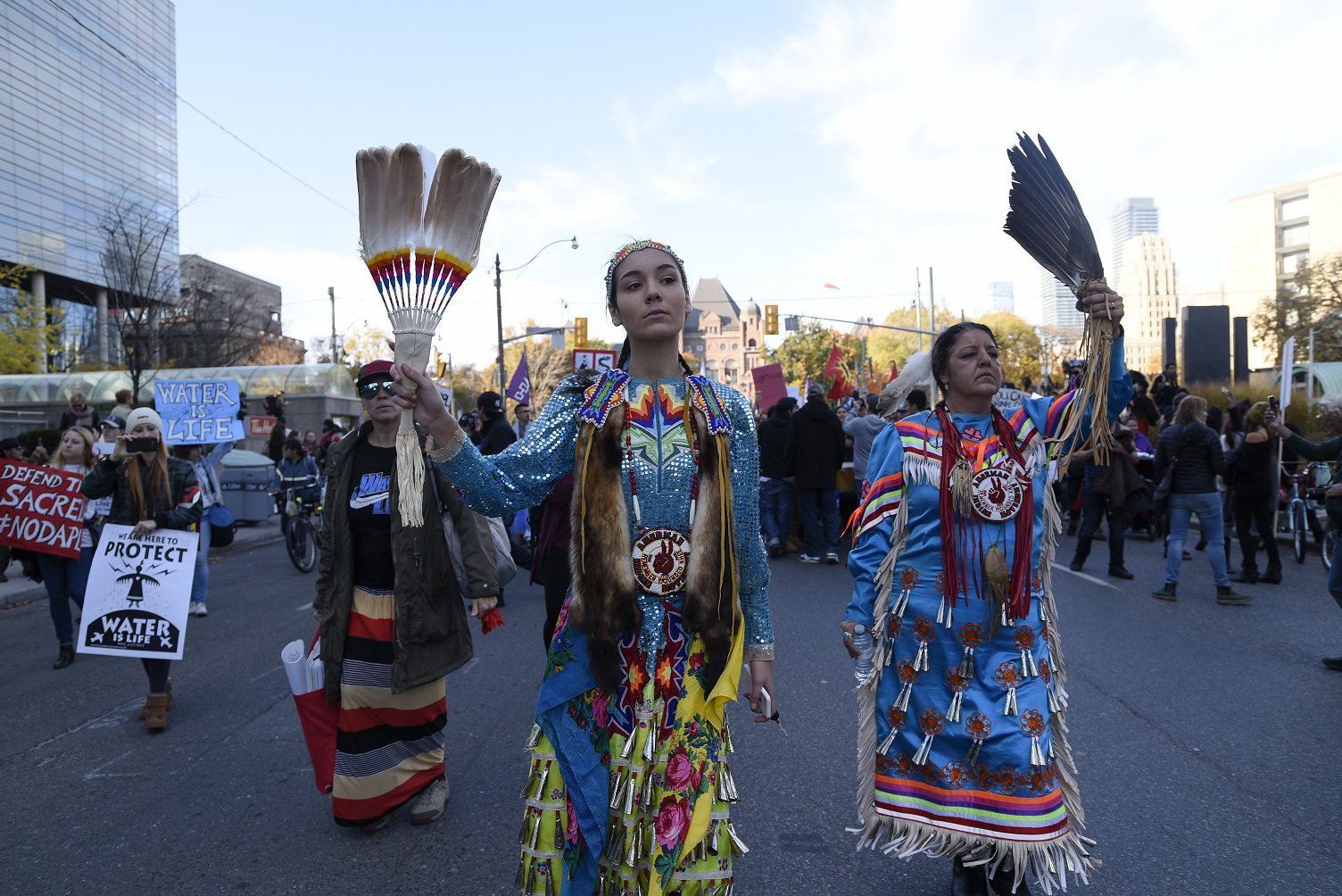 Women in traditional Indigenous dress protest on streets of Toronto